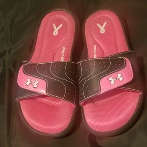 A pair of pink and black under armour slides.
